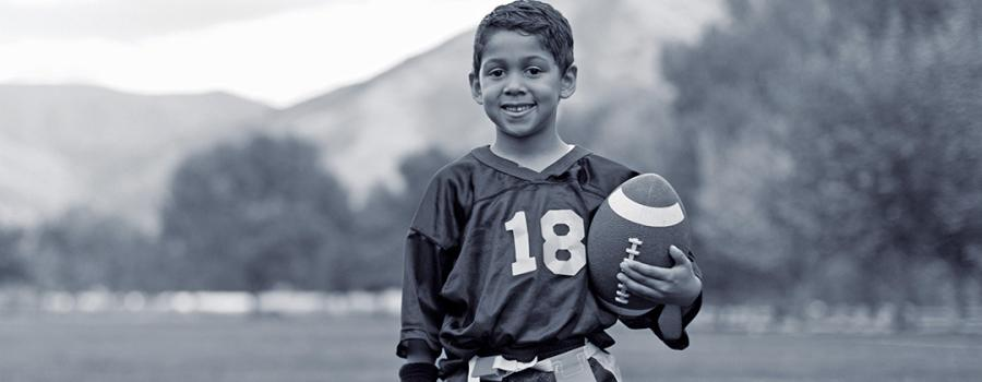 Photo of a young boy at football practice holding a football