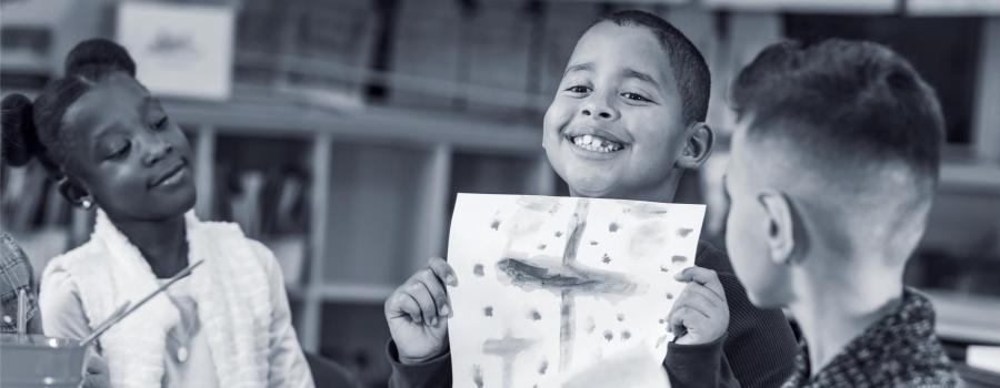 Photo of a young boy showing off his artwork to classmates